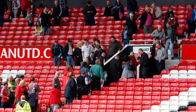 Aficionados del Manchester United abandonan el estadio.