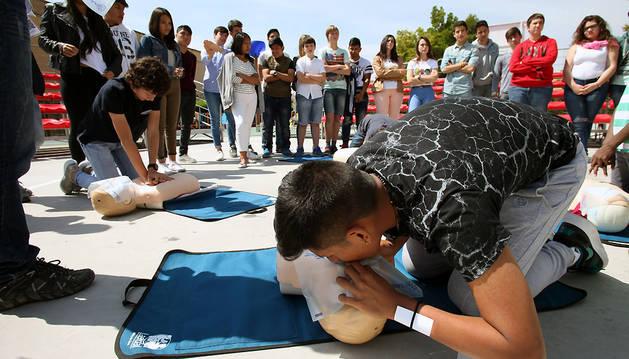 Dos alumnos del colegio de la Anunciata realizan prácticas de reanimación cardiopulmonar (RCP) ante la atenta mirada de sus compañeros.