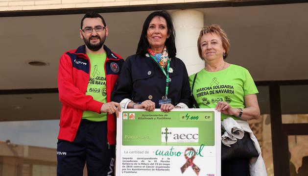 Jesús Mª Rodríguez, alcalde de Ribaforada, y Lola Arrondo, concejal de Fustiñana, entregan el cheque a Mamen Motilva (en el centro).
