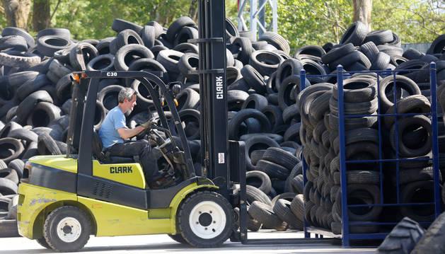 Un operario de Neumáticos Aizoáin selecciona ruedas. Esta empresa recoge el material desechado de Navarra, La Rioja y Álava.