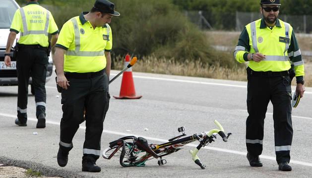 Dos guardias civiles pasan junto a la bicicleta del ciclista que ha muerto este miércoles en Alicante