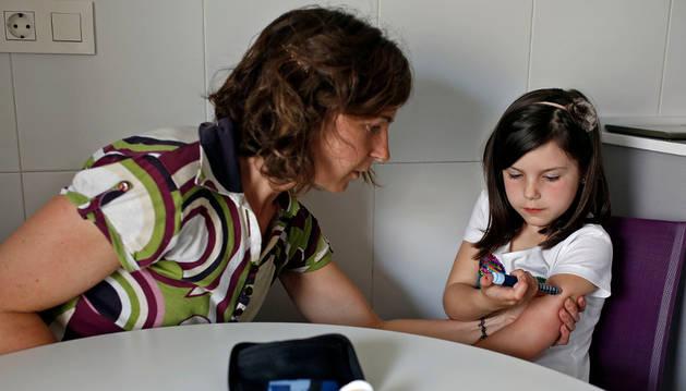 Naia Blanco García, de siete años y afectada de diabetes tipo I, se inyecta insulina con la ayuda de su madre, Yolanda García Aizpún.