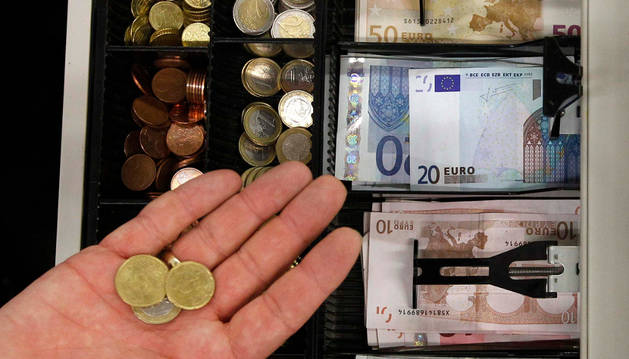 Monedas y billetes de euro en una caja registradora.