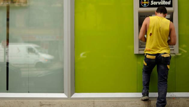 Un hombre saca dinero del cajero de una sucursal de Bankia de Madrid.