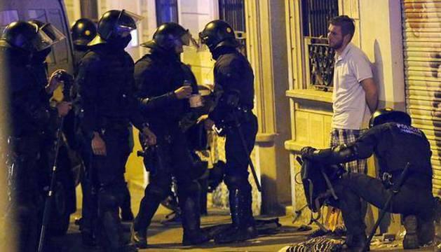 Miembros de los antidisturbios realizan un registro por las calles del barrio barcelonés de Gracia.