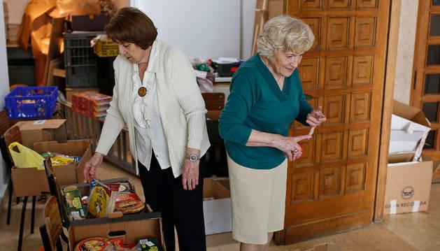 Milagros Sáinz Castillejo y Conchita Beldarrain Eugui revisan los lotes de alimentos tras realizar la distribución en la parroquia de La Paz.