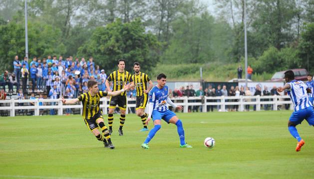 David González, delantero del Cirbonero, controla el balón ante la presión de tres rivales en el partido de ida ante el Cayón en Cantabria.