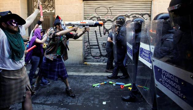 Un protestante con una pistola de agua, frente a la policía durante los disturbios.