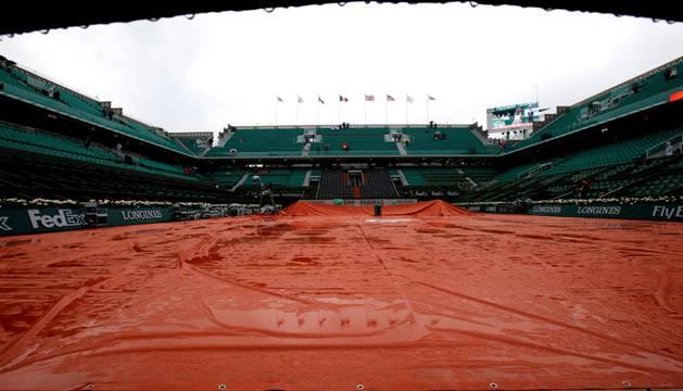 Una de las pistas del torneo francés de Roland Garros vacío por la lluvia al comienzo de la jornada 9 en Roland Garros, en París.