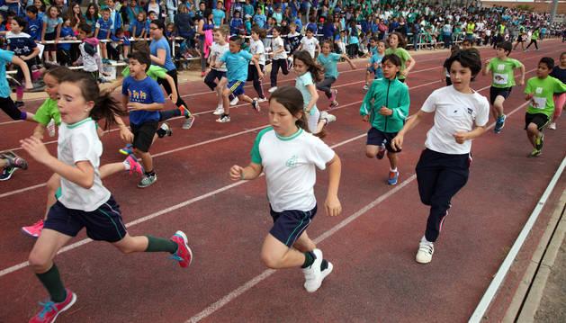Un grupo de escolares corre sobre la pista del estadio Nelson Mandela ante la mirada de sus compañeros de colegio ubicados en la grada.