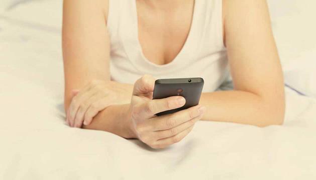 Una persona consulta el móvil en la cama.