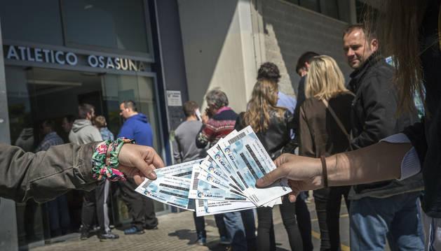 Unos aficionados muestran las localidades compradas ayer a primera hora de la tarde en las oficinas del estadio de El Sadar.