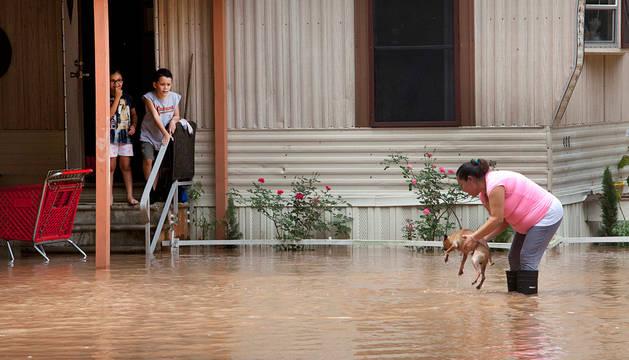Una mujer recoge a su perro tras la inundación del río Brazos en  Richmond, Texas.