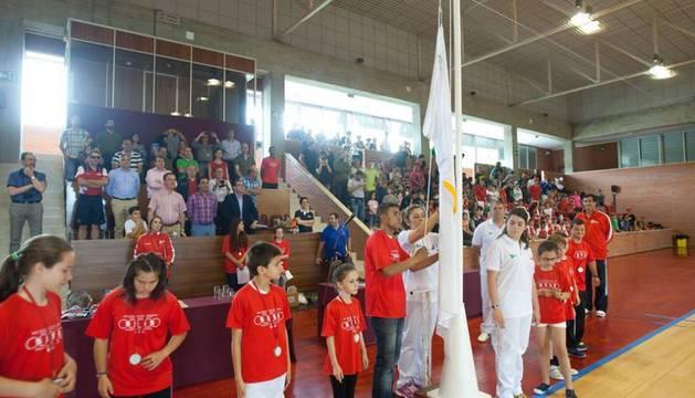 Un grupo de jóvenes levantan la bandera olímpica en el pabellón de la Universidad de Navarra.