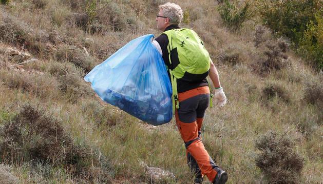 Un voluntario, con una bolsa cargada de basura, en la recogida que se efectuó en el monte octubre de 2015.