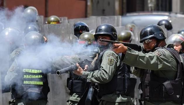 La políca venezolana lanza gas lacrimógeno a los manifestantes.