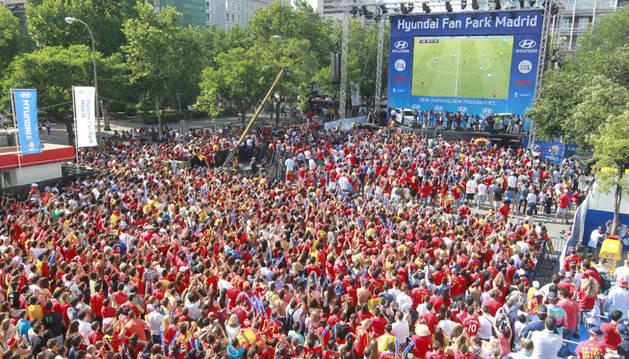 Varios aficionados viendo un partido de la selección española en una pantalla gigante.