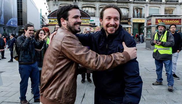 Los líderes de Podemos, Pablo Iglesias (d), y de IU, Alberto Garzón (i), dándose un abrazo en la Puerta del Sol,