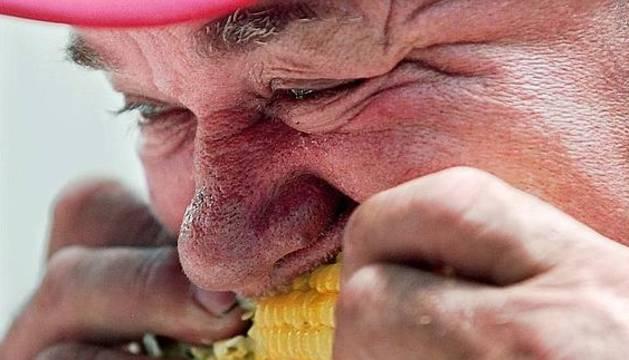 Anciano devora una mazorca de maíz.