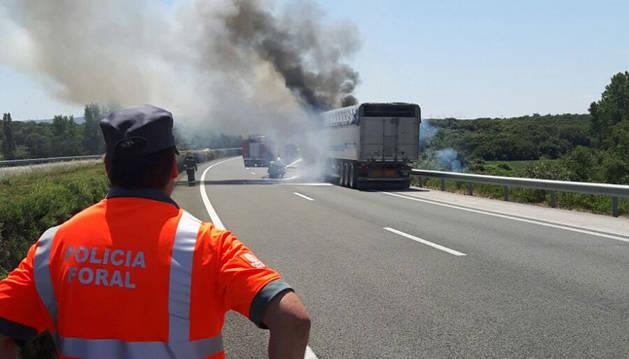 Un Policía Foral observa la columna de humo en el lugar del suceso.