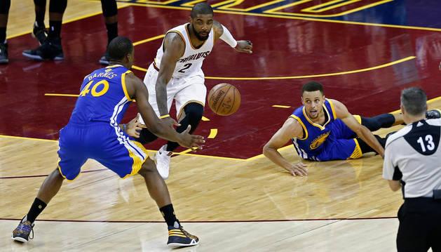 El jugador de los Cavaliers Kyrie Irving (2i) lucha por el balón con Stephen Curry (d) y Harrison Barnes (i) de los Warriors.