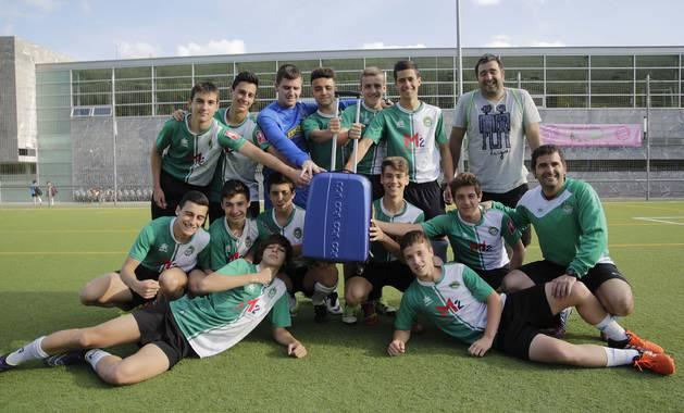 Los jugadores y entrenadores del Cadete A del Gazte Berriak posan junto a una maleta en el campo de fútbol de Ansoáin días antes de viajar a Málaga.