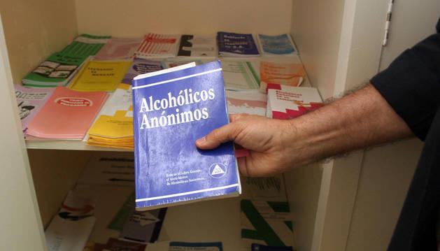Un hombre sostiene un libro de Alcohólicos Anónimos.