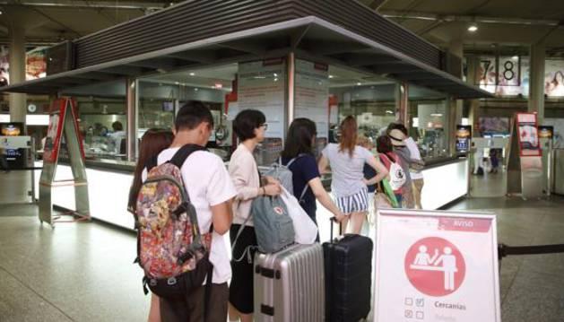 Colas de viajeros ante el punto de información de la estación de Atocha.