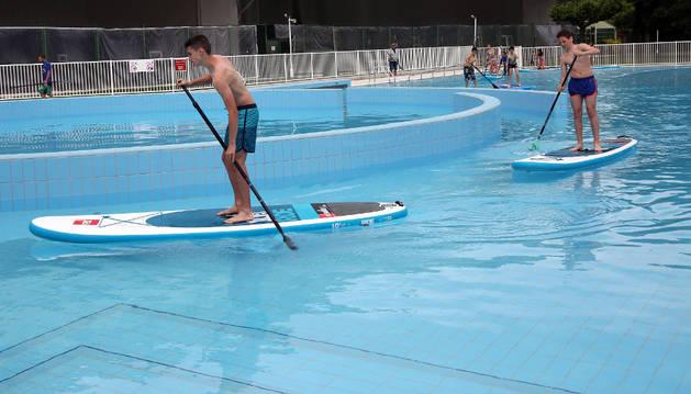 Un grupo de adolescentes sobre sus tablas aprovechando las olas de la nueva piscina.