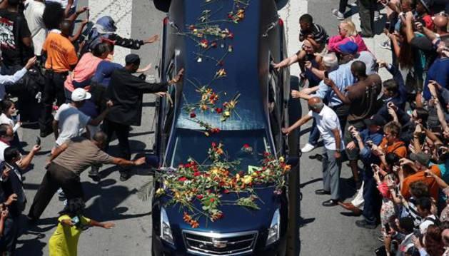 Ciudadanos de Louisville tocan el coche que ha trasladado el féretro de Mohamed Alí.