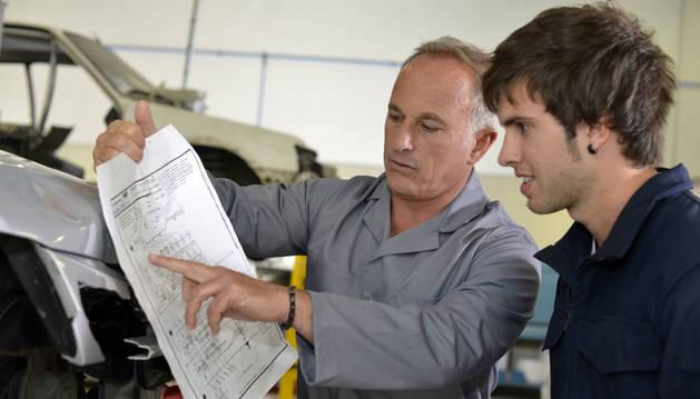 Un becario atiende las explicaciones que le da un compañero en un taller mecánico.