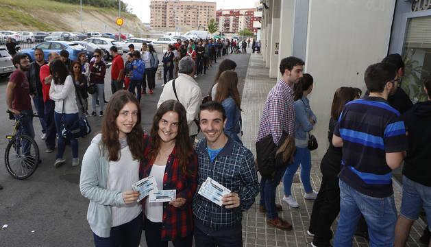 Tres aficionados rojillos posan orgullosos con sus entradas mientras cientos de personas hacen cola a sus espaldas para adquirir una.