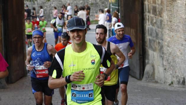Un participante en la media maratón del pasado año sonríe durante la subida. Tras el, dos maratonianos.