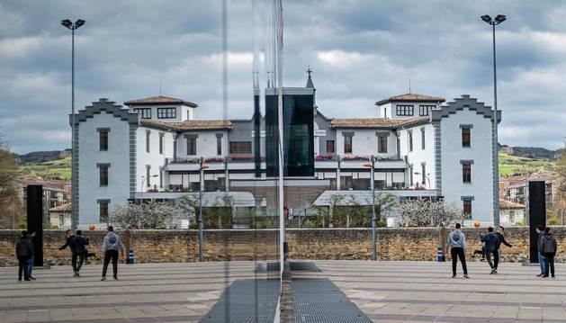 Imagen de la fachada acristalada del polideportivo, en la que se refleja la residencia San Jerónimo.