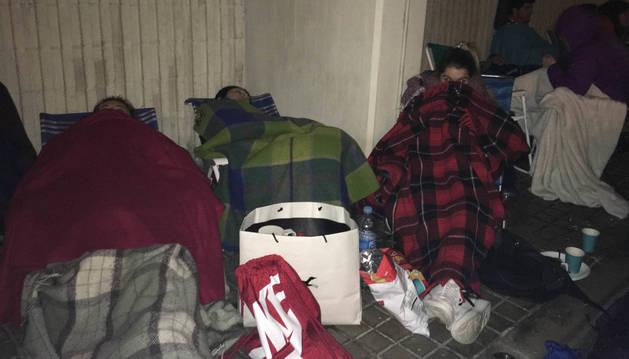 Tres aficionados intentan descansar tapados con mantas.