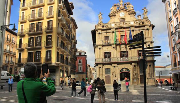 Un turista saca una foto de la plaza del Ayuntamiento.
