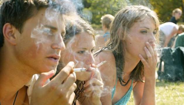 Jóvenes fuman mientras toman el sol en un parque.