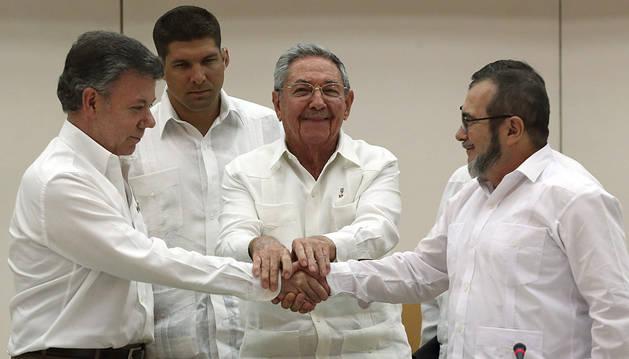 Raúl Castro aprieta las manos del presidente de Colombia Juan Manuel Santos y el máximo líder de las FARC, Rodrigo Londoño.