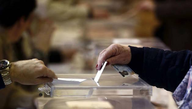 Una mujer introduce su voto en una urna de un colegio electoral de Pamplona.