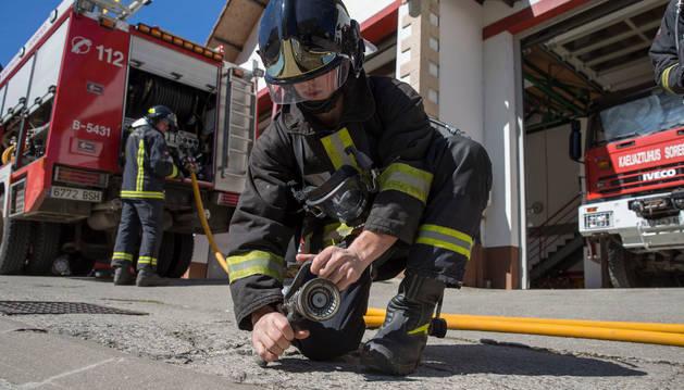 Un bombero prepara una manguera.