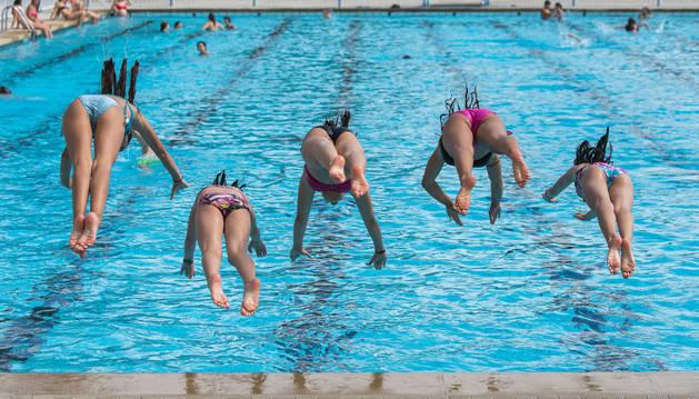 Un grupo de niñas saltando a una piscina.