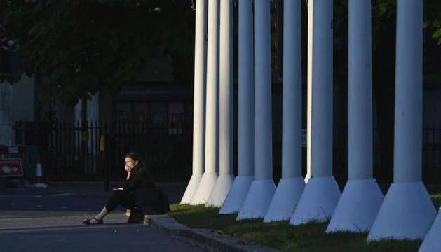 Una mujer descansa en una acera junto a las Casas del Parlamento durante el amanecer en Londres.