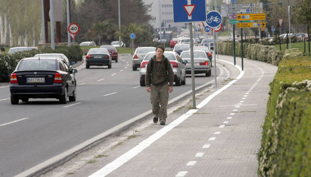 Un joven camina por la acera de la Avenida de Navarra.