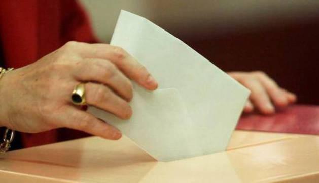 Una votante introduce su voto en la urna.