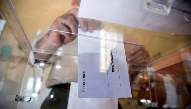 Una persona deposita en una urna de un colegio electoral.