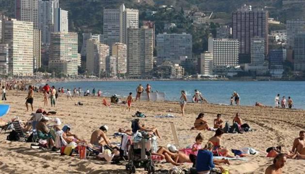 Turistas disfrutando del sol en la playa de Benidorm.