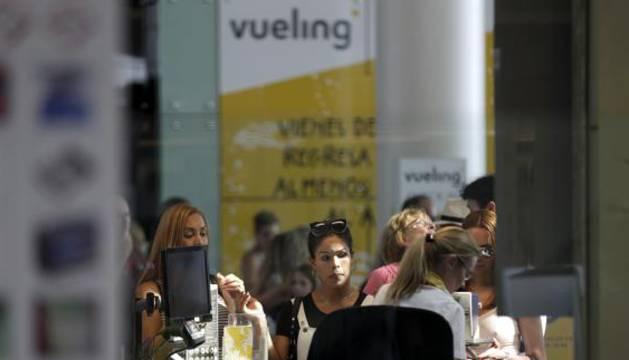 Personal de facturación de Vueling atiende a los viajeros en el Aeropuerto de El Prat.