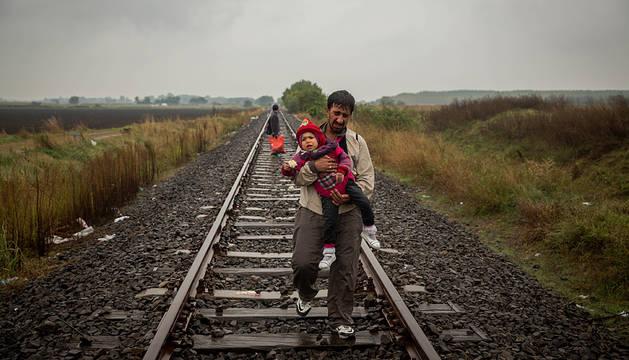 Un padre camina por las vias del tren llevando a su hijo en brazos unos cientos de metros despues de haber cruzado la frontera entre Serbia y Hungría.