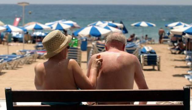 Pareja de turistas aplicándose crema solar en Benidorm.