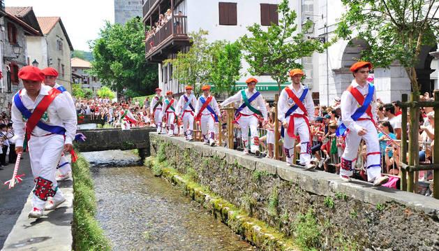 El grupo de Ezpatadantzaris bailando el 'Zubigainekoa' sobre los laterales del río Onín ante un numeroso público.